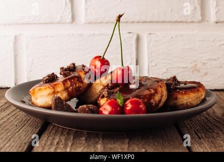 Il cibo della colazione gustosa concetto. La cheesecake, cheesecake, cagliata frittelle con ciliegie e cioccolato su uno sfondo nero da una tabella di cemento e un wh Foto Stock