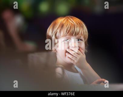 Happy little boy copre la sua bocca sorridente in serata Foto Stock