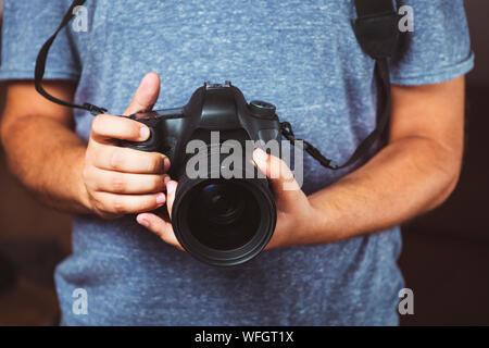 Close up uomo mani tenendo la fotocamera DSLR - Uomo fotografia con la fotocamera Foto Stock