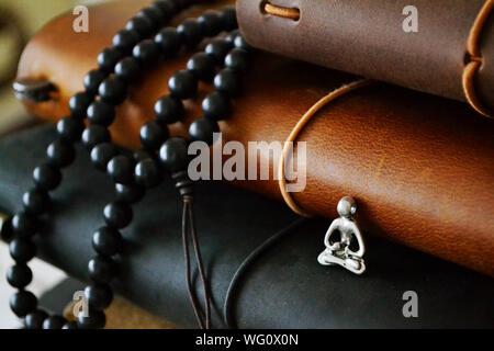 Close-up della collana di perle e figurine con libri Foto Stock