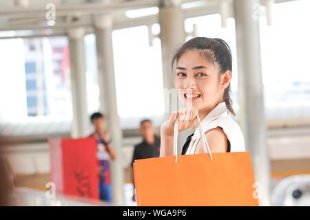 Vista laterale Ritratto di sorridente giovane donna azienda borse per lo Shopping nel ponte di coperta