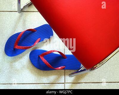 Angolo di Alta Vista di flip-flop sul pavimento da sedia Foto Stock