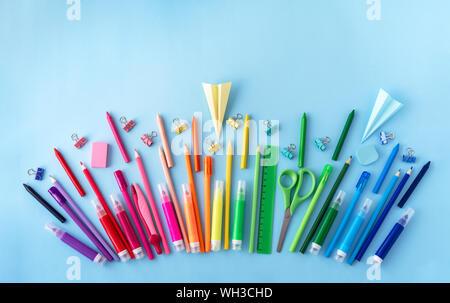 Varietà di forniture scolastiche in arcobaleno sequenza colori pastello su sfondo blu. Piatto stile di laici. Si torna a scuola concetto. Foto Stock