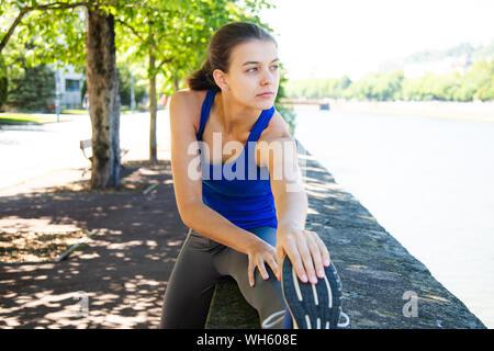 Cute girl teen in blu t-shirt facendo esercizi di stretching all'aperto Foto Stock