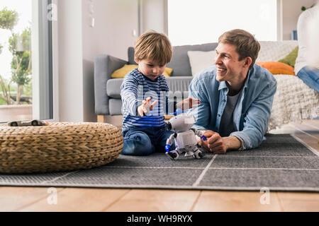 Padre e figlio giacente sul piano, giocando con robot giocattolo
