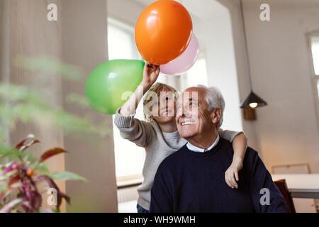 Felice nonno e nipote giocando con palloncini a casa Foto Stock