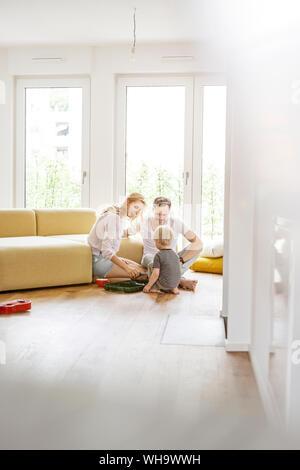 La famiglia felice con un figlio giocare nel loro salotto della nuova casa