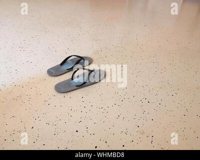 Angolo di Alta Vista di flip-flop sul pavimento Foto Stock