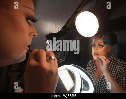 L'uomo con la riflessione a specchio mettendo sul rossetto Foto Stock