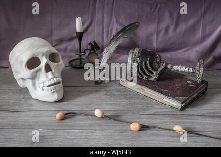 Cranio con inchiostro e penna del cappello sul tavolo