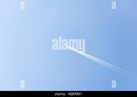 Luminoso Cielo di estate blu con un unico aereo commerciale battenti. Contrails seguire il piano come velocità attraverso l'aria. Foto Stock