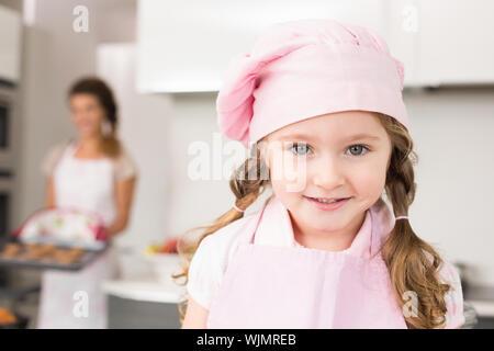 Bambina indossa grembiule rosa e gli chef hat sorridente in telecamera a casa in cucina Foto Stock