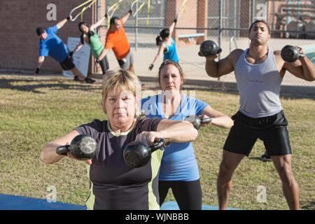 Donna matura e il gruppo esercita in outdoor boot camp classe fitness Foto Stock