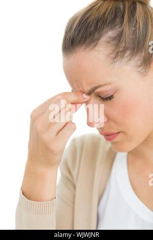 Donna con mal di testa pizzicando il suo naso e wincing su sfondo bianco Foto Stock