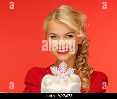 Donna in muffole e vestito rosso con il simbolo del fiocco di neve Foto Stock