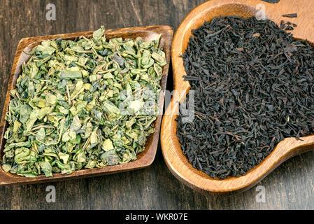 Close-up di estratto secco di tè alle erbe foglie in ciotole di legno sul tavolo Foto Stock