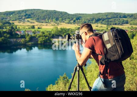 Fotografo di prendere foto di fauna selvatica, uomo con impostazione della fotocamera su un treppiede