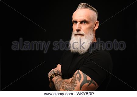 Ritratto fiduciosi, uomo duro con barba grigia e tatuati bracci Foto Stock