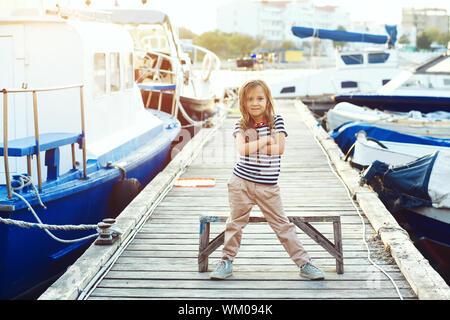 Bambino moda indossando vestiti della marina in stile marina in posa su legno ormeggio nel porto di mare