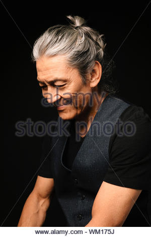 Ritratto sorridente, felice senior uomo che guarda in basso Foto Stock