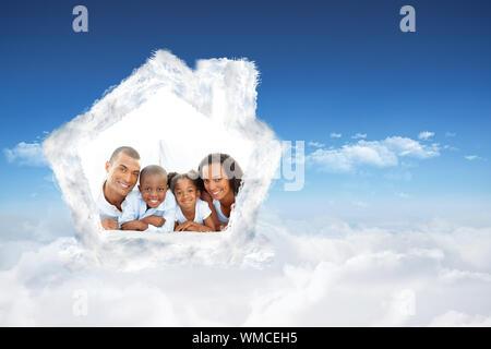 La famiglia felice avendo divertimento sdraiato sul letto contro blu luminoso cielo di nuvole Foto Stock