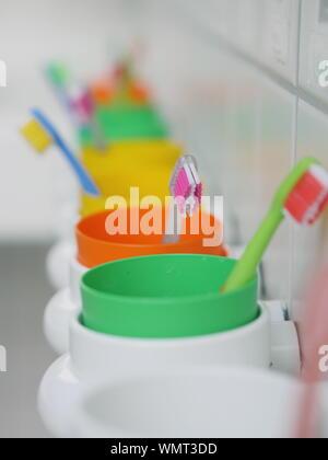 Close-up di spazzolini da denti colorati in contenitori a bagno