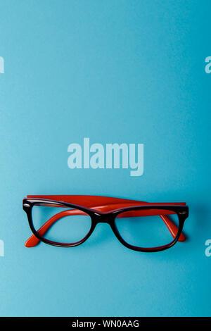 Coppia in plastica di colore rosso-occhiali bordati su uno sfondo blu Foto Stock