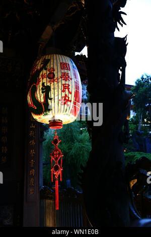 Basso angolo vista della lanterna cinese appeso dal tetto Foto Stock