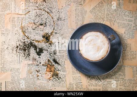 Ceramica Blu tazza di cappuccino oltre il vecchio giornale. Vista dall'alto. Foto Stock