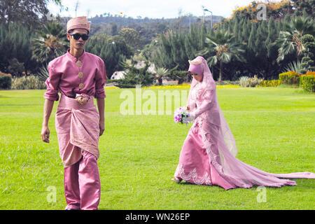 Fiducioso sposa e lo sposo in Abbigliamento tradizionale camminando sul campo erboso Foto Stock