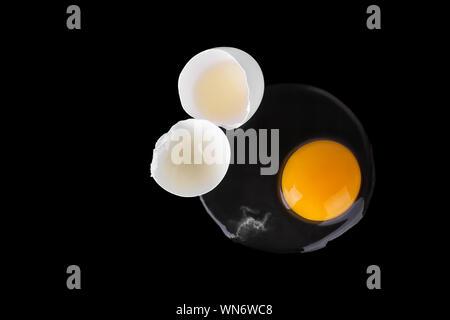 Rotture di bianco d'uovo crudo, rotondo giallo tuorlo, incrinato due metà di guscio d'uovo su sfondo nero isolato vicino la vista superiore, design insolito, banner di Pasqua Foto Stock