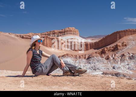 Bionda e giovane donna caucasica da sola seduta e ammirando la natura incontaminata della Valle della Luna nel Deserto di Atacama, Cile. Straordinario paesaggio sfondo con