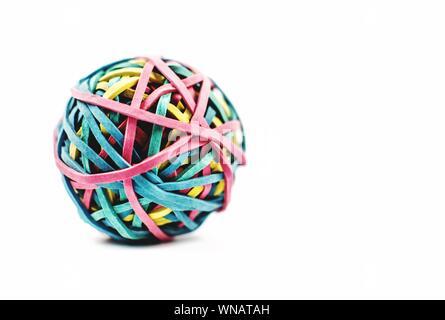 Close-up di una sfera realizzata con colorate bande di gomma contro uno sfondo bianco Foto Stock