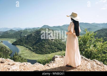 Bella donna elegante in un cappello si ammira una bellissima vista sul paesaggio naturale e Shkadar Lago in Montenegro