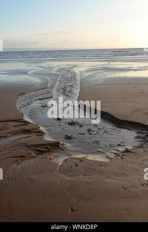 Il luogo dove un fresco molle di acqua entra nel mare su una spiaggia di sabbia con acqua fresca la pulsazione attraverso la sabbia e il mare.