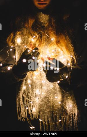 Giovane donna tenendo le luci di Natale all'aperto al buio Foto Stock