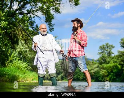 La pesca è divertimento. amici gli uomini con la canna da pesca e net. felice per i pescatori in acqua. hobby di imprenditore. Pensione di pesca. La pesca con la mosca avventure. pensionato padre e figlio maturo con la barba. Foto Stock