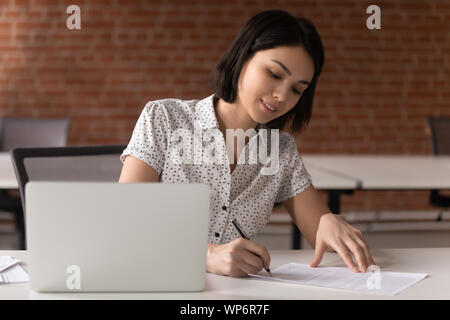 Sorridente femmina asiatica executive manager firma contratto di business. Foto Stock