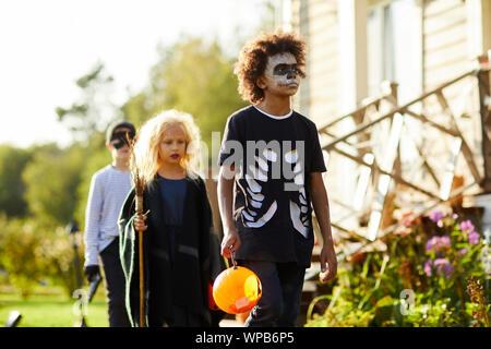 Multi-etnico gruppo di bambini trucco o trattare su Halloween, focus sul ragazzo afro-americano di indossare il costume e cestello di contenimento, spazio di copia