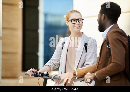 Vita su ritratto della moderna coppia giovane riding scooter elettrici in una strada di città, focus su dai capelli rossi donna sorridente allegramente, spazio di copia