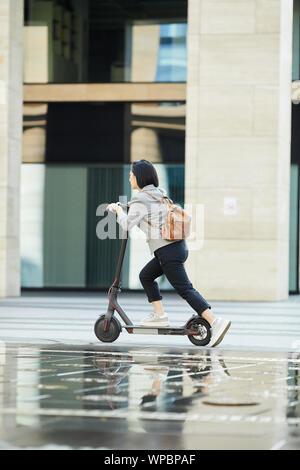 Lunghezza piena vista laterale della giovane donna asiatica di equitazione scooter elettrico veloce nella strada di città, spazio di copia