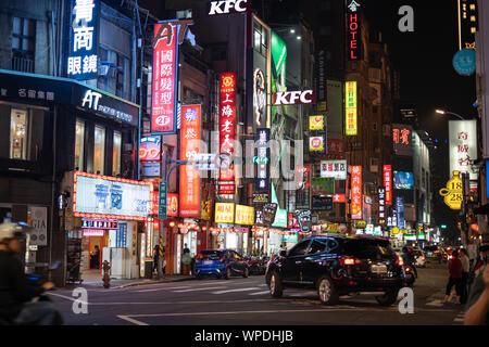 Taipei, Taiwan: strada urbana notturna illuminata da colorate pubblicità, insegne al neon con i caratteri cinesi. Foto Stock