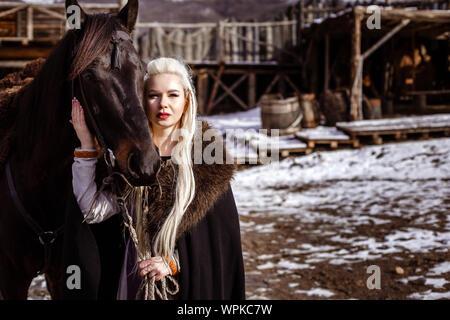 All'esterno ritratto della bella furious guerriero scandinavo lo zenzero donna in abiti tradizionali con collare di pelliccia, con la spada in mano e V in legno Foto Stock