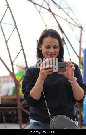 Ragazza con uno smartphone in mani all'aperto. Giovane madre prende le immagini sul telefono di un bambino Foto Stock