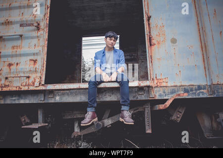 Angolo basso ritratto di Giovane triste seduto su abbandonato treno merci