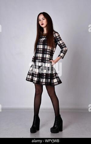 Ritratto di giovane donna che indossa motivo a scacchi abito in piedi sul pavimento contro la parete Foto Stock