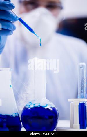 Donna scienziato in apparecchiature di protezione usando una pipetta con la caduta di una soluzione di blu nel laboratorio di ricerca. Foto Stock