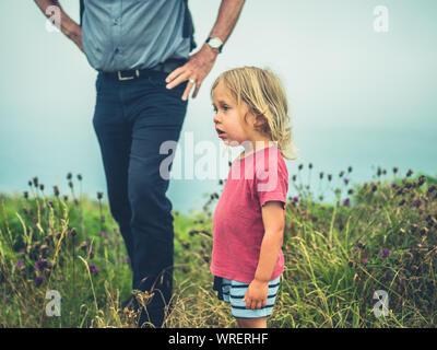 Un piccolo bimbo è a piedi dalla costa con il suo nonno in un giorno nuvoloso. Autentico stile di vita della famiglia shot. Foto Stock