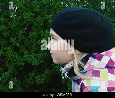 Vista laterale della ragazza che indossa Knit Hat guardando lontano contro piante Foto Stock