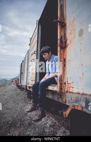 Triste giovane uomo seduto sulle chiamate abbandonate treno merci contro Sky